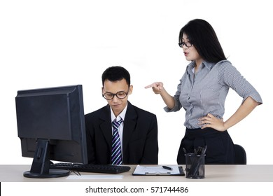 Portrait of young boss feels angry to her employee while standing in front of computer, isolated on white background