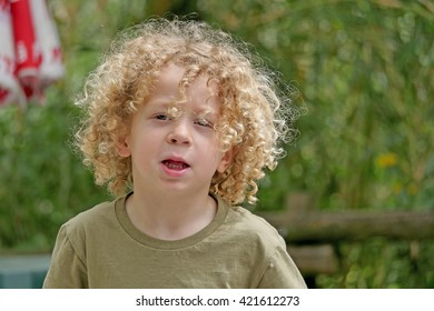 a portrait of a young boy with blond curly hair
