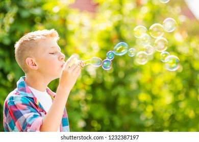 Portrait of a young boy blowing soap bubbles in a park