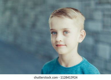 Portrait of a young boy with blue eyes in a blue T-shirt