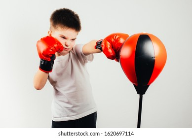 Portrait of young boy boxer in red boxing gloves