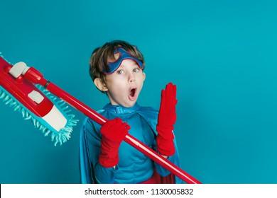 Porträt von jungen Jungen, die Superhelden reinigen, halten Mop auf blauem Hintergrund