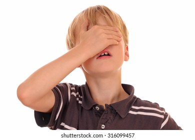 Portrait of a young boy covering his eyes on white background