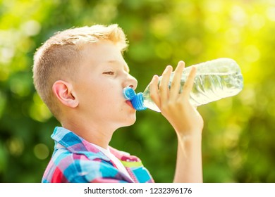 Portrait of a young boy drinking a bottle of water