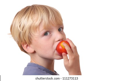 Portrait of a young boy eating a tomato