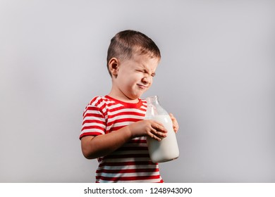 Portrait of young boy with eyes closed making faces isolated over gray background - studio shot. Child with bottle of milk against grey background.