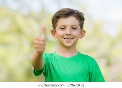 Portrait of young boy giving a thumbs up in park