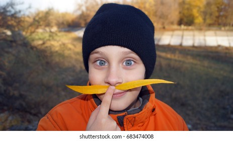 Portrait young boy holding a fingers mustache of leaves up to his face