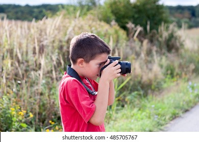 A portrait of a young boy, holding a modern digital camera