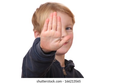 Portrait of a young boy holding out hand, indicating stop