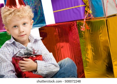 Portrait of young boy looking at camera with boxes near by