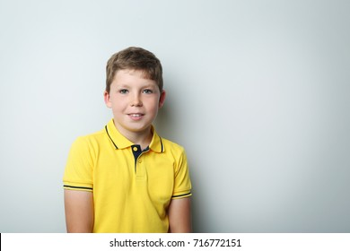 Portrait of young boy on grey background