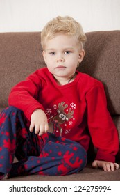 Portrait of young boy in pajama sitting on the sofa