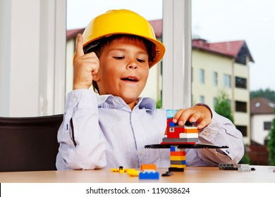 Portrait of young boy posing at home with lego in helmet
