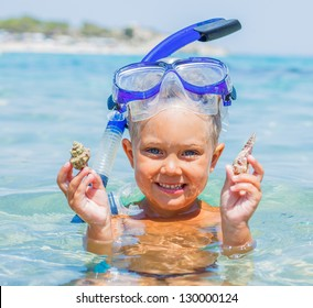 Portrait of young boy with seashells in snorkling equipment swimming in the transparent sea