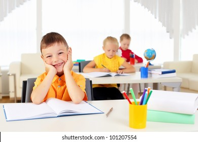 Portrait of a young boy sitting at his desk at school