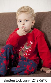 Portrait of young boy sitting on sofa in pajama