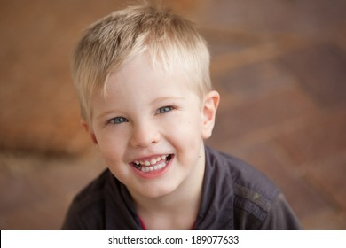 A portrait of a young boy smiling and looking at the camera.  The child looks relaxed and happy.