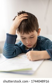 Portrait of young boy struggling with his homework at home. Children home education concept. Distance learning