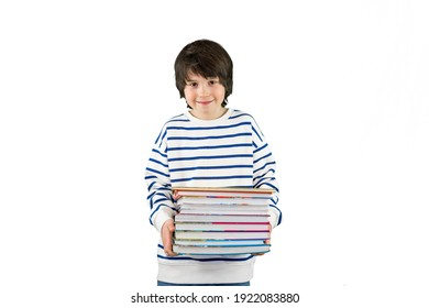 Portrait of a young boy of ten years old wearing striped t shirt, holding large books in his hands. Child smiling at the camera, isolated on white background, copy space.