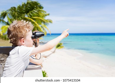 portrait of young boy using binoculars and pointing at something with finger at beautiful tropical fiji island with turquoise lagoon in the background, copy space on right