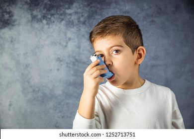 Portrait of young boy using a inhaler