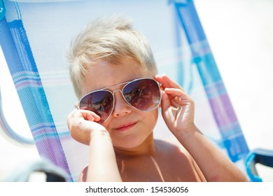 Portrait of young boy wearing sunglasses relaxing on beach.