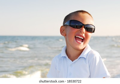 Portrait of young boy wearing sunglasses and posing by sea.