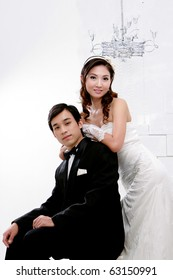 Portrait of young bride and groom in romantic action on white background