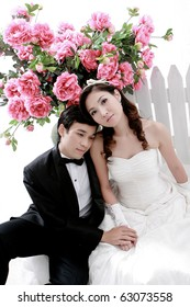 Portrait of young bride and groom sitting together with flower background