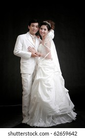 Portrait of young bride and groom standing in black background