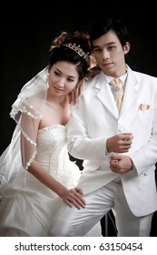 Portrait of young bride and groom in white dress in black background
