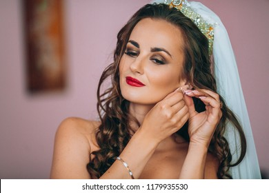 The portrait of the young bride at a window - the girl prepares for a wedding and dresses accessories, earrings. The face of the bride with a stylish hairstyle Before wedding ceremony and first look.
