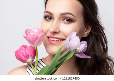 Portrait of young brunette beautiful woman with makeup in striped dress, standing and holding tulips and looking at camera with toothy smile. indoor studio shot, isolated on light grey background.