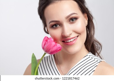 Portrait of young brunette beautiful woman with makeup in striped dress, standing and holding pink tulip and looking at camera with toothy smile. indoor studio shot, isolated on light grey background.