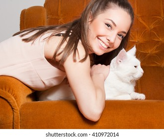 Portrait of young brunette beauty holding gorgeous white cat.
