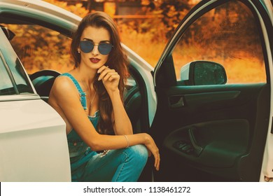 Portrait of young brunette in blue sunglasses in the car in the autumn time