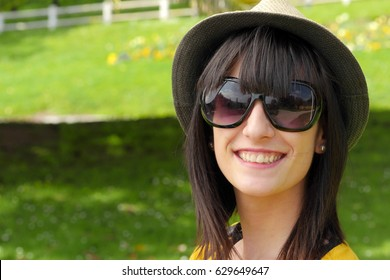 portrait of young brunette girl with summer hat in park, outside