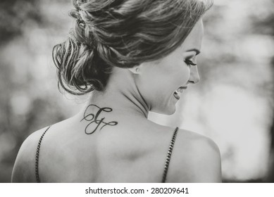 Portrait of young brunette girl with tattoo on the neck