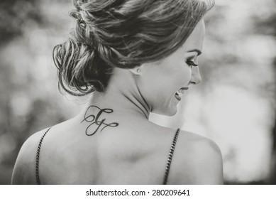Portrait d'une jeune brunette avec tatouage au cou