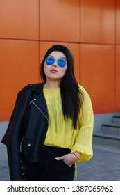 Portrait of a young brunette plus size woman. Audacity pan-Asian girl in a biker leather jacket with sunglasses poses near a bright wall. Body positivity movement. Street fashion. Leisure time