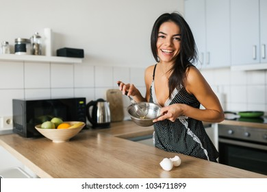 portrait of young brunette pretty woman cooking scrambled eggs in kitchen in morning, smiling, happy mood, positive housewife, healthy lifestyle, laughing, having fun