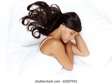 Portrait of a young brunette sleeping in bed