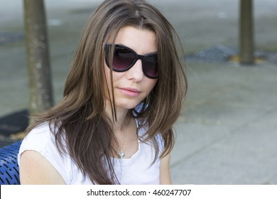 Portrait of young brunette in sunglasses outdoors