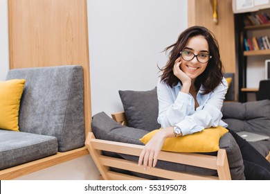 Portrait young brunette woman in black glasses chilling on couch in modern office space. Comfortable, cheerful mood, smiling to camera. Place for text