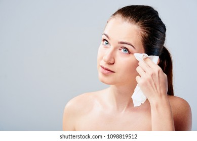 Portrait of a young brunette woman cleaning her face with wet wipes. Girl is removing make-up with facial tissues isolated on grey background. Beauty skin care concept.