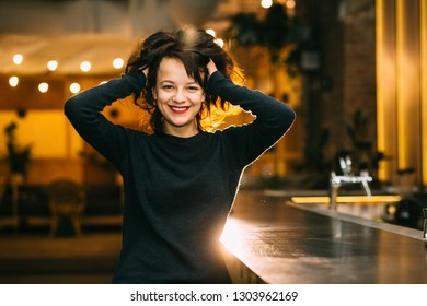Portrait of young brunette woman in evening time relaxing sitting near bar counter in a empty pub. Older teen girl ruffling hair in night club or bar. Alcohol addiction concept.