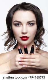 Portrait of young brunette woman. Girl with lipstick in hand. Female lips beauty makeup concept.
