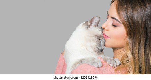 Portrait of a young brunette woman and her cat.