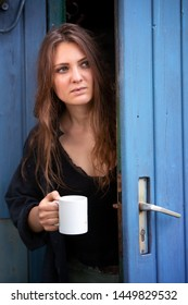 portrait of young brunette woman holding cup and standing at blue door